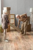 Photo full length of senior man suffering from backache while rolling carpet with wife