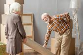 senior muž trpí bolestí zad při válcování koberec s manželkou