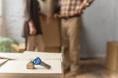 Photo keys lying on cardboard box on foreground and blurred view of senior couple, moving concept