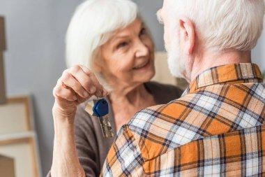 Senior woman holding keys and hugging husband, moving concept stock vector