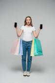 šokovaná žena drží mobilní telefony s prázdnou obrazovkou a nákupní tašky na šedý, černý pátek koncept