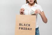 oříznutý pohled na ženu držící kreditní karty a nákupní tašku s černým pátečním nápisem izolovaným na šedé