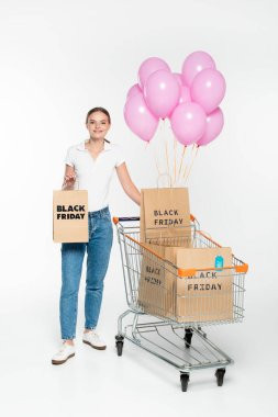 Young woman holding shopping bag with black friday lettering near cart and pink balloons on white stock vector