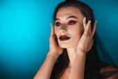 mladá žena s černým make-up dotýkat vlasy a dívá se pryč na modré