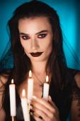 selektivní zaměření mladé ženy s černým make-upem a závojem v blízkosti hořících svíček na modré