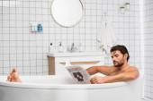 Szakállas férfi, üzleti betűkkel az újságon, otthon fürdik.