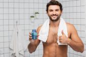 Usmívající se muž s ručníkem kolem krku ukazující palec nahoru a držení po holení krém v koupelně