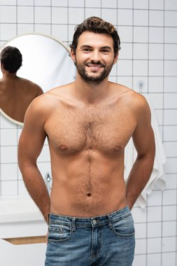 Muscular man in jeans smiling at camera in bathroom stock vector
