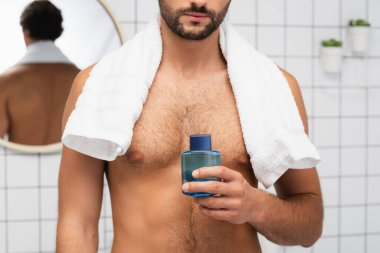 Cropped view of shirtless man with towel around neck holding after shaving lotion in bathroom stock vector