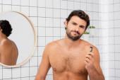 Muž bez trička s ranou na tváři při pohledu do kamery při držení břitvy v koupelně