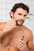 Muž bez trička ukazuje na ránu na tváři, zatímco drží břitvu v koupelně