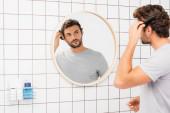Fiatal férfi néz kamera közben fésülködés haj elmosódott előtérben a fürdőszobában
