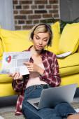 junge blonde Frau beim Webinar und zeigt auf das Diagramm
