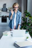 junge blonde Frau mit Brille bei Online-Konferenz und winkender Hand