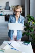 junge blonde Frau mit Brille arbeitet von zu Hause aus und hält Laptop