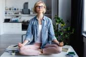 junge blonde Frau mit Brille sitzt in Lotus-Pose auf Tisch