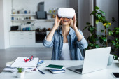 excited blonde woman in vr headset near laptop