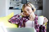 fiatal szőke nő fülhallgatóban dolgozik otthonról és teát iszik