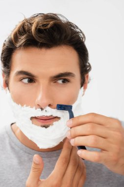 Young man with foam on face shaving with disposable razor isolated on grey stock vector