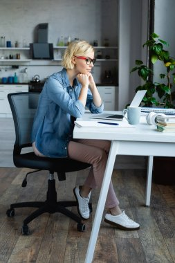 Full length of young blonde woman in eyeglasses working from home stock vector