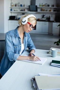 Gözlüklü genç sarışın kadın not defterine notlar yazıyor.