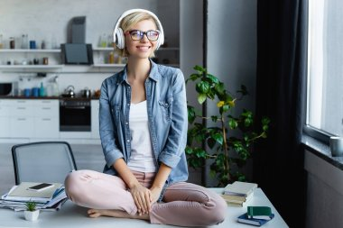 young blonde woman in eyeglasses listening music and sitting on table