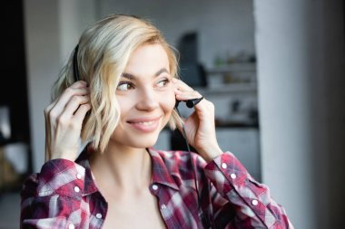 young blonde woman in checkered shirt putting on headphones