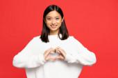 boldog és fiatal ázsiai nő mutatja szívjel a kezét elszigetelt piros