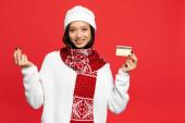 usmívající se asijská žena v klobouku a šálu držící kreditní kartu a ukazující peníze gesto izolované na červené