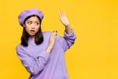 Asijská žena v baretu ukazuje žádné gesto s rukama izolovaných na žluté