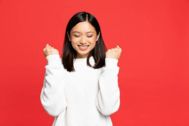 Young asian woman with closed eyes rejoicing and smiling isolated on red stock vector