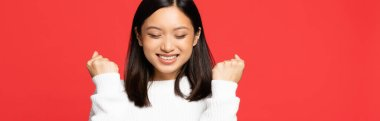 Happy and young asian woman with closed eyes rejoicing isolated on red, banner stock vector