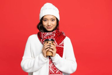 Happy asian woman in hat and scarf holding disposable cup with coffee to go isolated on red stock vector