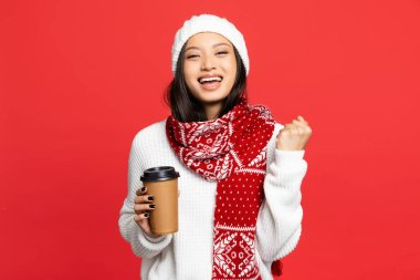 Excited asian woman in hat and scarf holding disposable cup and rejoicing isolated on red stock vector