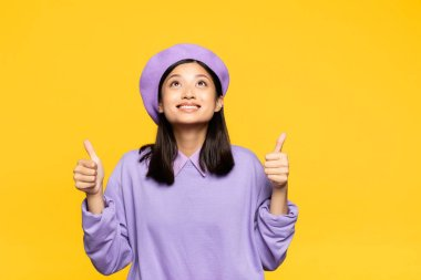Happy asian woman in beret showing thumbs up and looking up isolated on yellow stock vector