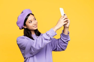 Happy asian woman in beret taking selfie on smartphone isolated on yellow stock vector