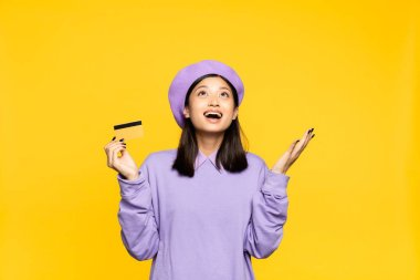 Excited asian woman in beret holding credit card and looking up isolated on yellow stock vector