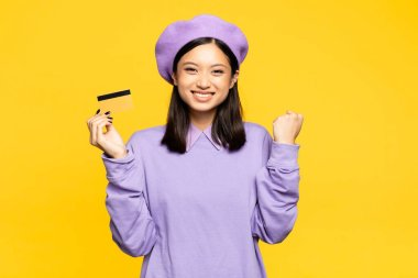 Excited asian woman in beret holding credit card and rejoicing isolated on yellow stock vector