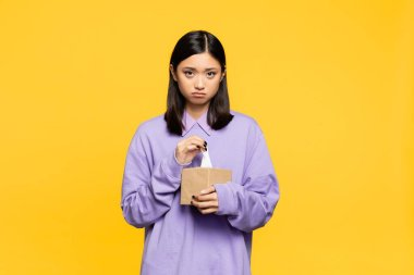 Sad asian woman holding tissue box isolated on yellow stock vector