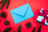 top view of gift box, cones, spruce branches and blue envelope on red background