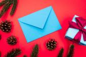 horní pohled na dárkové krabice, kornouty, smrkové větve a modrá obálka na červeném pozadí