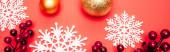Draufsicht auf Kugeln, Schneeflocken und Beeren auf rotem Hintergrund, Banner