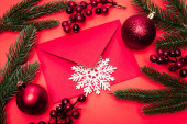 top view of Christmas decoration and envelope on red background