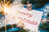 Veselé vánoční přání, dekorace a jiskra na modrém pozadí