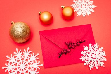 Top view of snowflake, baubles and envelope on red background stock vector