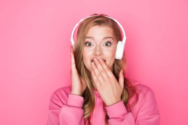 shocked beautiful woman listening music in headphones and covering mouth on pink background