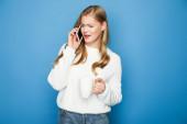 zavaros szőke nő pulóver beszél okostelefon bögre elszigetelt kék háttér