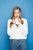 besorgt blonde schöne Frau im Pullover mit Becher isoliert auf blauem Hintergrund