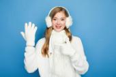mosolygós gyönyörű nő télen fehér ruhát mutató kéz a kesztyűt elszigetelt kék