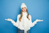 confused beautiful woman in winter white outfit showing shrug isolated on blue